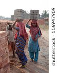 SARBERIA,INDIA, JANUARY 16: Brick field workers carrying complete finish brick from the kiln on January 16, 2009 in Sarberia, West Bengal, India. - stock photo