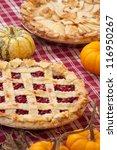 Cherry pie with lattice top, and apple pie on fall themed napkin, and mini pumpkins. - stock photo