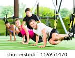 Group of people exercising with suspension trainer in fitness club or gym - stock photo