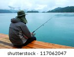 Man fishing near lake from jetty - stock photo