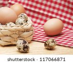 Quail and hen eggs on kitchen table with a towel - stock photo
