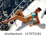 Attractive young girl in blue bikini posing on a yacht at a sunny summer day - stock photo