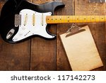Vintage black double cutaway guitar on old wood surface and old clipboard,  good for playlists, and production notes. one piece maple neck. - stock photo