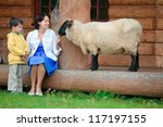 Young woman and her little son feeding a sheep - stock photo