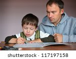 Father helping son doing homework - stock photo