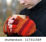 Woman in bright red mittens holding a hot drink - stock photo