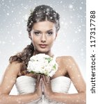 Young attractive bride with the bouquet of white roses over snowy Christmas background - stock photo