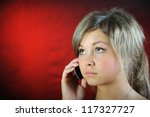 The girl, speaking on phone. On red background. - stock photo