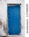 Old painted blue door on the whitewashed wall. Background. Typical for Greece... - stock photo