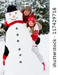 Winter fun, snowman -  family enjoying winter - stock photo
