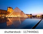 PARIS-APRIL 16: Reflection of Louvre pyramid shines at dusk during the Summer Exhibition April 16, 2010 in Paris. Louvre is the biggest Museum in Paris displayed over 60,000 sq.M. of exhibition space. - stock photo