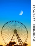 ferris wheel in the evening with moon in the sky - stock photo