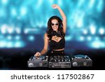 Jubilant sexy female disc jockey standing behind her mixing deck laughing and holding up her hand against a backdrop of blue party lights with copyspace - stock photo