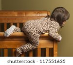 Toddler climbing out of her crib. - stock photo