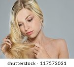 Portrait of blond girl checking hair ends - stock photo