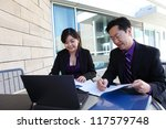 Attractive man and woman Chinese business team working on laptop computer - stock photo