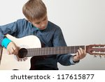 13 year old teenage boy concentrating on playing acoustic guitar. - stock photo