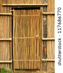 A handmade bamboo door leading to a native dwelling - stock photo