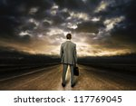 Business man standing in the middle of the road. Dramatic sky above - stock photo