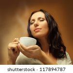 Beautiful woman drinking coffee or tea - stock photo