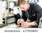Cook, the pastry chef, in hotel or restaurant kitchen cooking, he is finishing a sweet dessert - stock photo