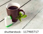 Little white box of tablets as sweetener for a mug of coffee - stock photo