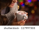 Closeup on hot chocolate with marshmallows in hand of happy woman - stock photo