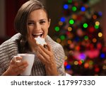 Happy woman eating Christmas cookie and drinking hot chocolate - stock photo