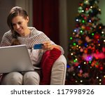 Happy woman with laptop and credit card in front of Christmas tree - stock photo