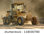 Large road grader working ground at a new commercial housing development - stock photo