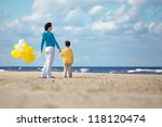 Mother and little son with yellow balloons on the beach on beautiful summer day - stock photo