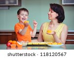 Smiling young mother and her little son baking muffins in the kitchen - stock photo