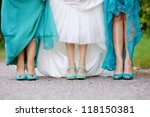 Bride and bridesmaids show off their shoes at wedding - stock photo