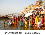 VARANASI, INDIA - APRIL 23: Unidentified people taking ritual bath in the river Ganga on April 23, 2011 in the holy city of Varanasi, India. The holy ritual bath is held every day. - stock photo