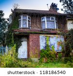 A derelict house with ivy growing over it - stock photo