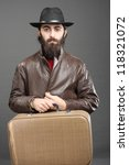 Traveler with suitcase, dressed in jacket and hat and beard. - stock photo