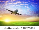 Jet aircraft over the field of green at sunset - stock photo
