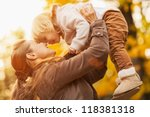 Young mother rising baby up - stock photo