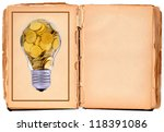 Old damaged hand-book with golden lightbulb and blank for your text - stock photo