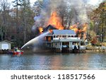 TIGER, GA, USA - NOV. 9: A fire boat on the water sprays a large house fire on November 9, 2012 on Lake Burton in Tiger, Georgia. - stock photo