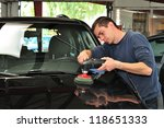 Worker polishing a car. - stock photo