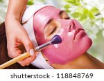 Young beautiful woman with moistening fruit facial mask at beauty salon - stock photo