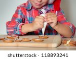 Close up of kid decorating the gingerbread cookies, Merry Christmas - stock photo