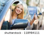 Young woman doing thumps-up in car - stock photo