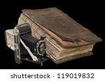 The old Christian Bible near the ancient camera. Isolated on the black - stock photo