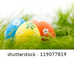 Three colorful Easter eggs hidden in a fresh green grass - stock photo