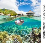 Woman snorkeling in clear tropical waters in front of overwater bungalows - stock photo