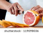 Horizontal shot of female hands cutting a grapefruit, close-up - stock photo