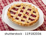 Cherry pie with lattice top on fall themed napkin, and mini pumpkins. - stock photo