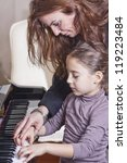 Piano player and her student during lesson - stock photo